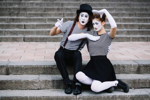Pantomimepaare, die auf dem treppenhaus bilden gesten sitzen