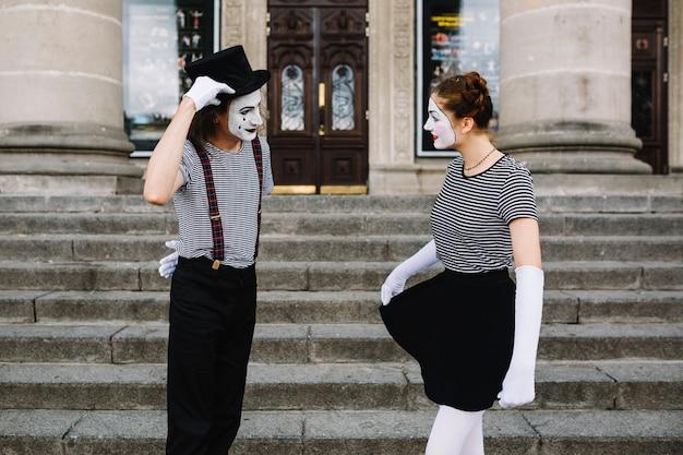 Pantomimepaare, die einander vor treppenhaus betrachten