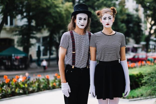 Pantomimepaare, die im garten stehen
