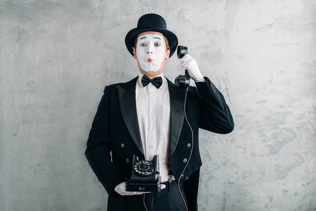Pantomimeschauspieler, der mit retro-telefon auftritt