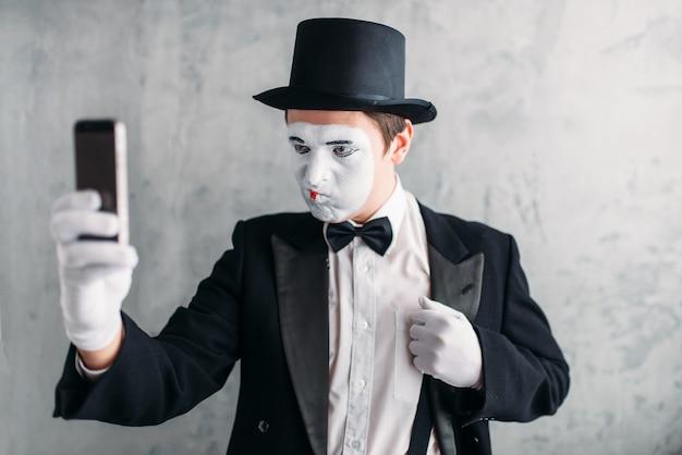 Pantomimeschauspieler mit make-up-maske macht selfie