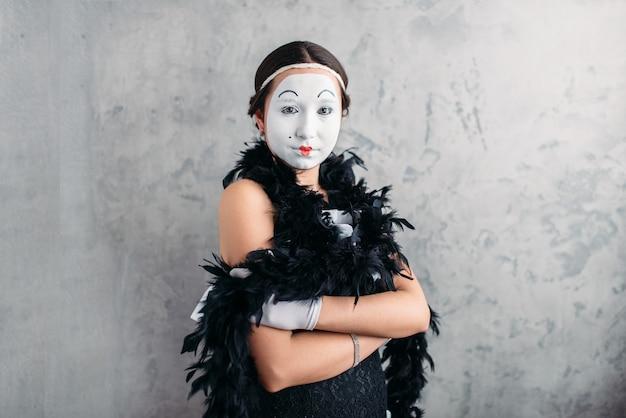 Pantomimeschauspielerin mit weißer make-up-maske, die im studio aufwirft.