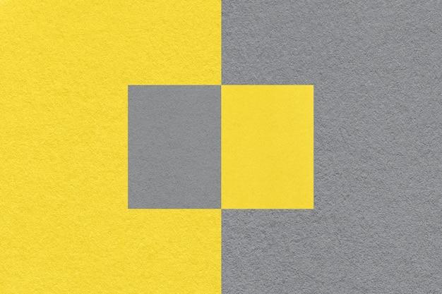 Pantone-trendfarbe des jahres 2021 leuchtendes gelb und ultimatives grau. textur des alten neutralen grauen papierhintergrundes, makro. moderner hintergrund mit geometrischer form.