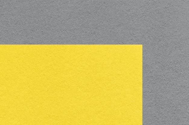 Pantone-trendfarbe des jahres 2021 leuchtendes gelb und ultimatives grau. textur des alten neutralen grauen papierhintergrundes, makro.
