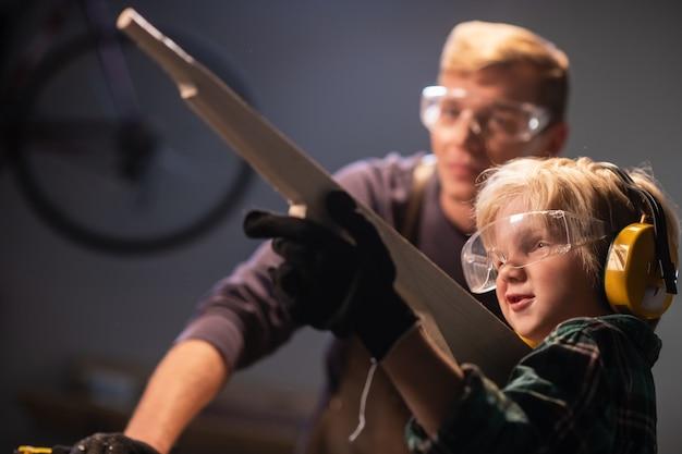 Papa, ein zimmermann, hat eine holzpistole für seinen sohn geschnitzt und der junge ist glücklich mit dem geschenk.