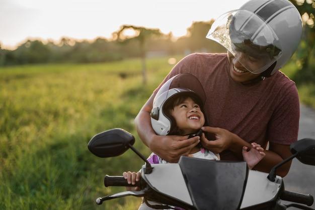 Papa hilft ihrer tochter, den helm zu befestigen Premium Fotos