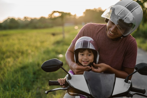 Papa hilft ihrer tochter, den helm zu befestigen