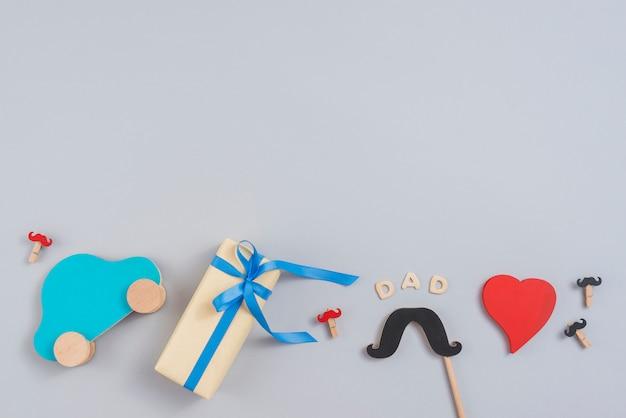 Papa inschrift mit geschenkbox, spielzeugauto und papierschnurrbart