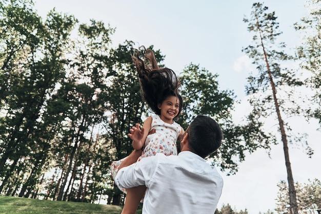 Papa ist ihr bester freund. junger liebevoller vater, der seine lächelnde tochter trägt, während er freizeit im freien verbringt
