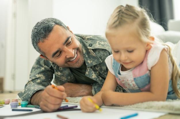 Papa lächelt. fröhlicher bärtiger papa lächelt beim malen des stammbaums mit tochter
