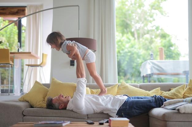 Papa liegt auf dem sofa und hebt sein kind im sonnenlicht durch die fenster in die luft