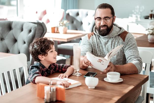 Papa liest. barded vater trägt graues hoodie-lesebuch für seinen sohn, der auf bestellung in der cafeteria wartet