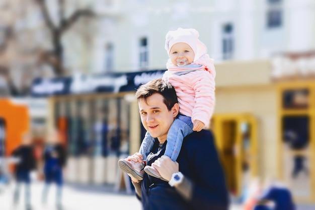 Papa mit baby an den schultern gehen auf der straße