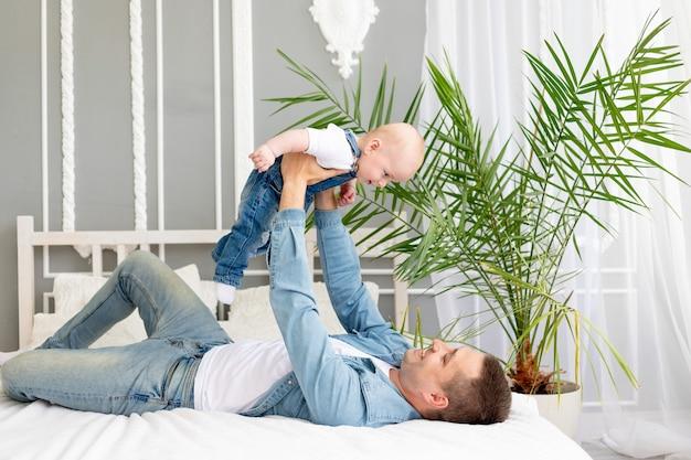 Papa mit baby im arm zu hause auf dem bett