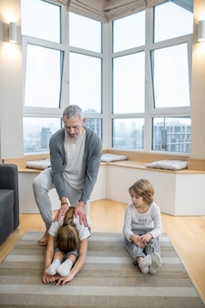 Papa mit kindern beim morgendlichen aufwärmen auf dem boden