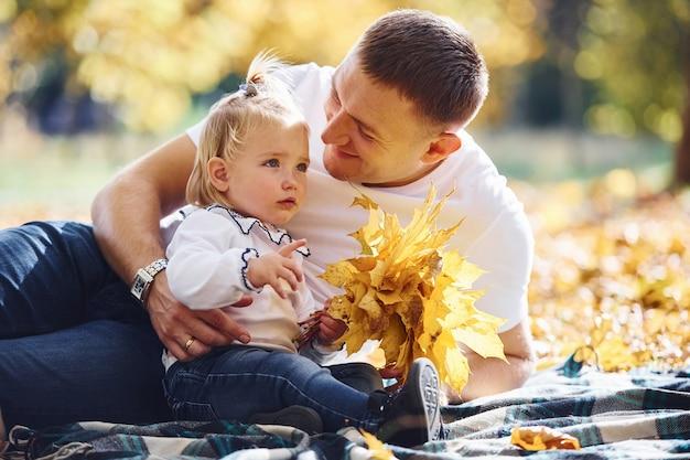 Papa mit kleiner tochter ruht sich am sonnigen tag in einem schönen herbstpark aus.