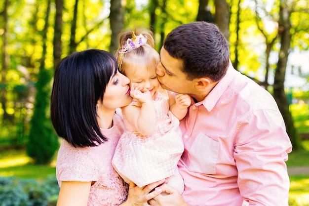 Papa mit mama küssen ihr kind während ihrer geburtstagsfeier sanft