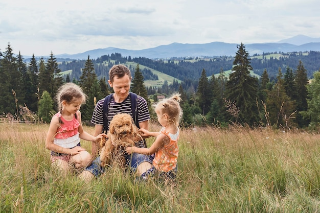 Papa mit zwei kleinen töchtern und einem hund auf einer lichtung vor dem hintergrund der berge