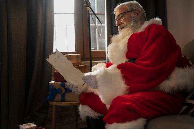 Papa noel auf der couch liest einen brief