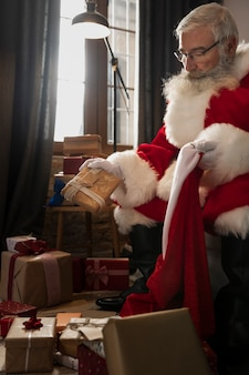 Papa noel, der ein eingewickeltes weihnachtsgeschenk hält