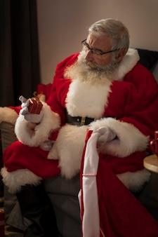 Papa noel mit einem kleinen geschenk in der hand