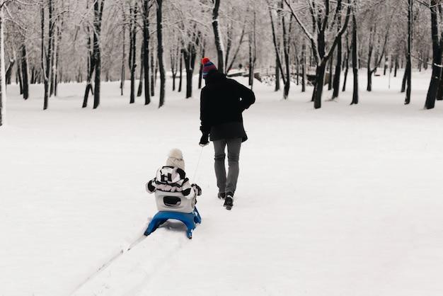 Papa reitet einen süßen jungen in einem schlitten im schnee, aktiver lebensstil, winter, familie