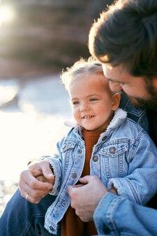 Papa sitzt und umarmt ein lächelndes kleines mädchen an einem kieselstrand am meer
