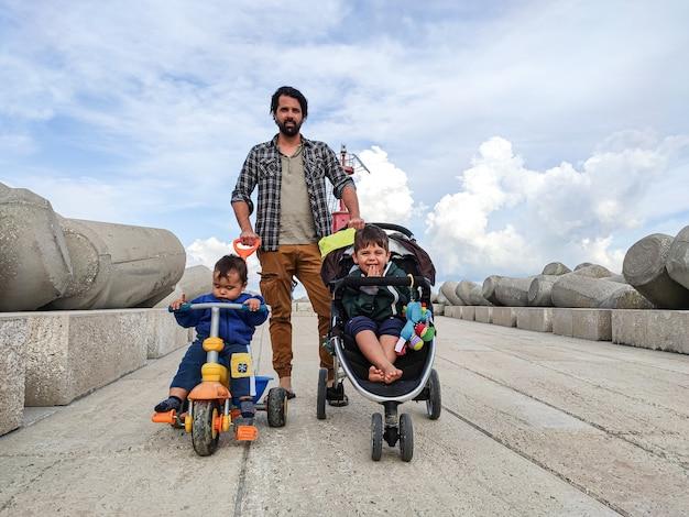 Papa spaziert mit zwei babys an einem bewölkten tag