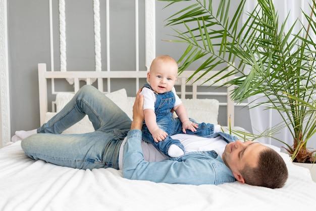 Papa spielt auf dem bett mit babysohn, glückliche vaterschaft