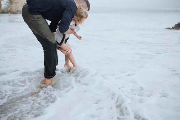 Papa spielt mit ihrer tochter und den wellen