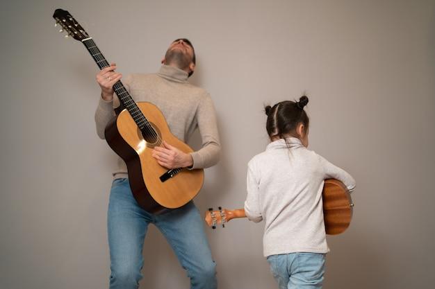 Papa spielt mit seiner tochter gitarre. das kind lernt mit einem tutor ein musikinstrument zu spielen. musikalisches duett eines vaters mit kind.