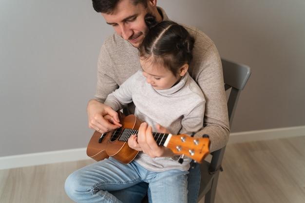 Papa spielt mit seiner tochter gitarre.