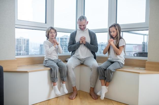 Papa und kinder mit geschlossenen augen sitzen auf der fensterbank