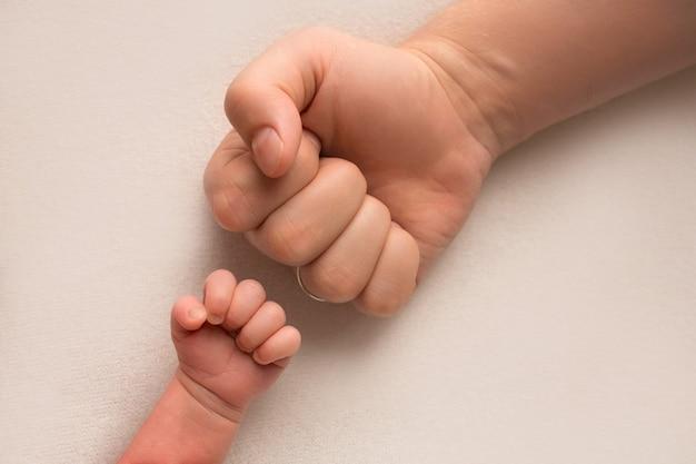 Papa und neugeborener sohn halten ihre hände in einer faust, kleinen und großen fäusten. vater und sohn, der erste boxschlag. foto in hoher qualität