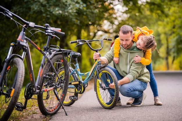 Papa und tochter inspizieren das rad des kinderfahrrads auf dem herbstpfad des parks.