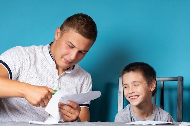 Papa unterrichtet das kind zu hause, homeschooling. vater hilft seinem sohn bei den hausaufgaben, scherenschnitt