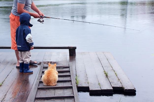 Papa zeigt seinem kleinen sohn, wie man mit einer katze fischt, die in der nähe wartet