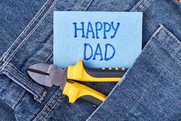 Papas grußpapier und jeans. zange an der tasche in der nähe der karte. wie man dem vater gratuliert.