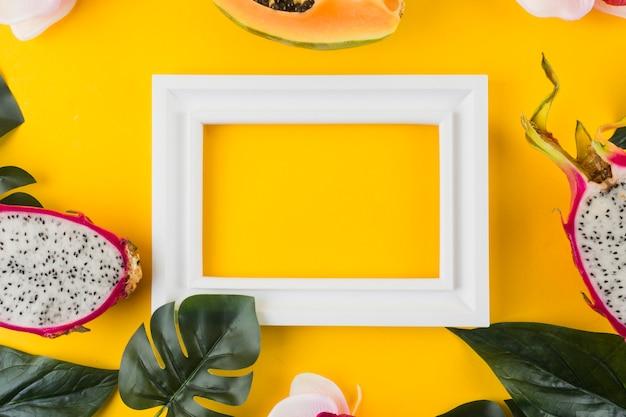 Papaya; drachenfrucht; blätter um den leeren weißen rahmen vor gelbem hintergrund