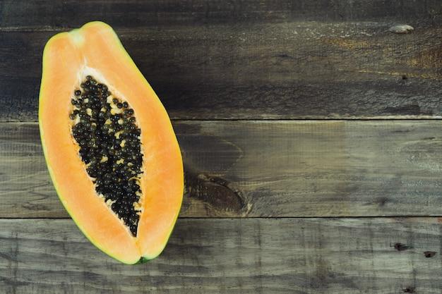 Papaya halbiert auf hölzernem hintergrund. speicherplatz kopieren. draufsicht.