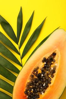 Papaya und palmblatt auf gelbem hintergrund.