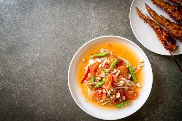 Papaya würziger salat mit gegrilltem hähnchen - traditioneller thailändischer street food-stil