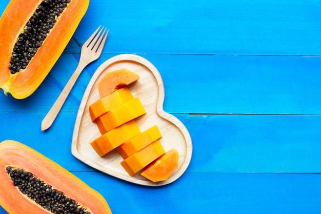 Papayafrucht auf blauem hölzernem hintergrund