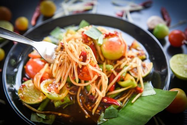 Papayasalat auf einem würzigen thailändischen selektiven fokus des lebensmittels des gabelgrün-papayasalats auf dem tisch som tum thai