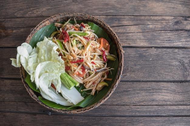 Papayasalat ist ein populärer behälter in thailand. würziges nahrungsmittel rufen sie namen som-tum an.