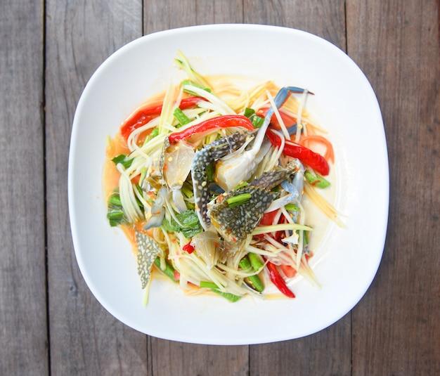 Papayasalat mit blauen krabben / thai food rohen krabben würzigen salat meeresfrüchte und gemüse auf holztisch