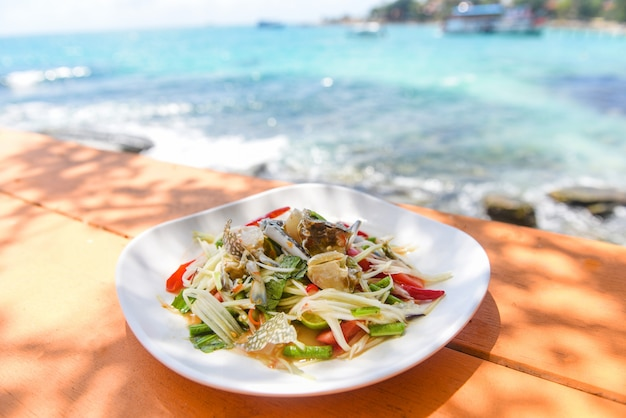 Papayasalat mit blauer krabbe auf tisch und strandmeerküstenhintergrund / thailändisches essen roher krabben würziger salat meeresfrüchte und gemüselebensmittel auf dem meereskonzept