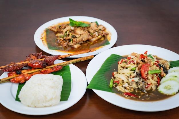Papayasalat mit gegrilltem hähnchen, würziger gegrillter schweinefleischsalat, nam tok moo. thailändisches nordöstliches essen.