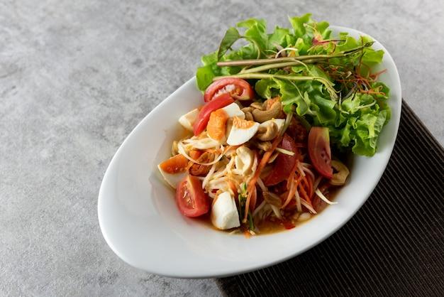 Papayasalat mit gesalzenen eiern auf einem teller-, somtum- oder thailändischem papayasalat