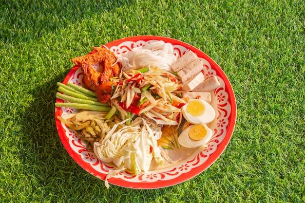 Papayasalat (som tum) tablett würzig auf grünem gras, thailändisches lokales essen draufsicht, nahaufnahme.